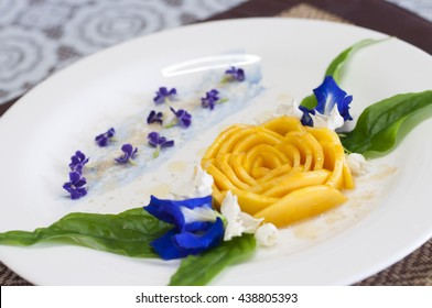 Food presentation of yellow mango fruit with rose shape on white dish.