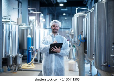 Food processing plant interior with positive smiling technologist holding checklist. Industrial worker satisfied with results and quality control.