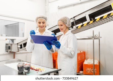 food production, industry and people concept - happy women technologists with clipboard tasting ice cream quality at factory
