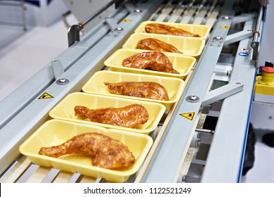 Food products meat chicken in plastic packaging on the conveyor