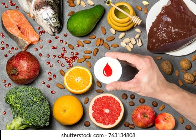 Food products useful for blood. Set of natural food products are sources of vitamins and minerals. Man's hand holds tag with homemade application from paper - symbol of blood. Top view
