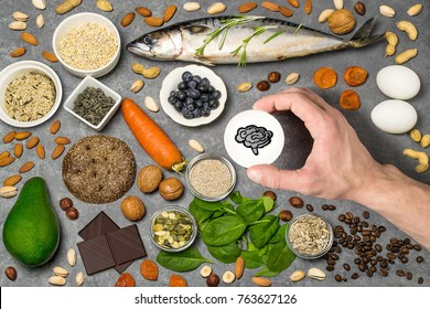 Food products useful for brain function. Set of natural food products are sources of vitamins and minerals. Man's hand holds tag with homemade application from paper - symbol of brain. Top view