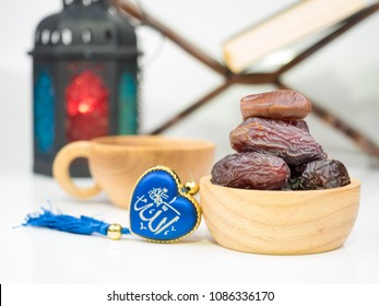 "food of ramadan kareem night composed of sweet dried fruits on white background,  with rosary with arabic text of the name of God ""Allah"""