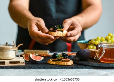 Food recipe concept. Toasts of cheese, figs and honey in hands in the kitchen. This Fig and Gorgonzola tartines, toast, bruschetta. drizzled with honey.