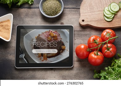 Food recipes tablet computer on rustic wooden table