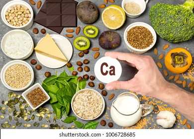 Food rich in calcium. Various natural sources of vitamins and micronutrients. Useful food for health and balanced diet. Prevention of avitaminosis. Man's hand holds tag with name of calcium