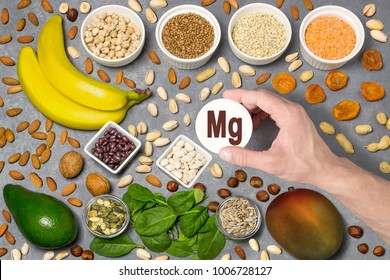 Food rich in magnesium (Mg). Various natural sources of vitamins. Useful food for health and balanced diet. Prevention of avitaminosis. Man's hand holds tag with name of magnesium. Top view