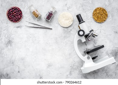 Food safety. Wheat, rice and red beans near microscope on grey background top view copy space