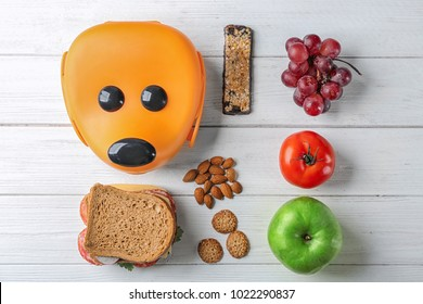 Food for schoolchild and lunch box on wooden background