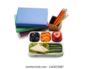 Food for schoolchild in lunch box and stationery on white background