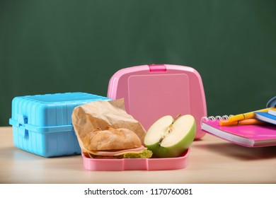 Food for schoolchild in lunch boxes with stationery on table
