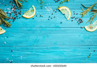 Food seasoning background. Blue coloured rustic wooden background, lemon slices, herbs, pepper, sea salt. Preparing a dinner. Space for text. Close-up. Vivid food frame. Top view. Cooking ingredients