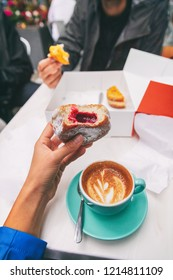 Food selfie girl eating a berry filled berliner donut while drinking a cappuccino coffee cup at cafe . City urban tourists travel lifestyle, POV of tourist foodie woman holding delicious doughnut .