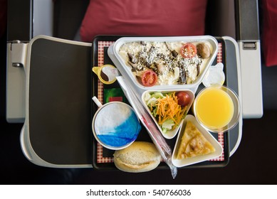 Food served on board of airplane on the table. Fresh meal with salad and orange juice for passenger. Italian tasty cuisine, risotto with mushrooms.  Top view