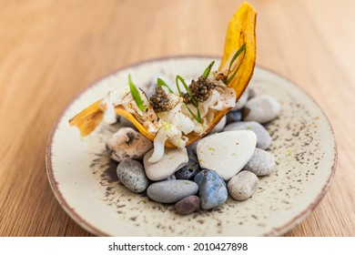 Food served on the plate at luxurious dinner at home. Banana chifles with fake squid noodles and beluga caviar on wooden table served for lunch.