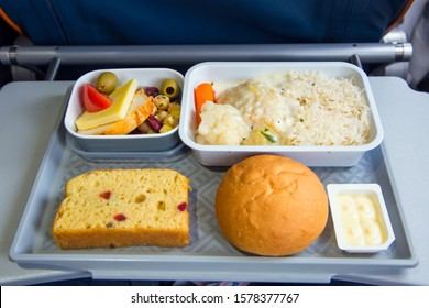 Food served in a passenger aircraft during the flight. Meal on the tray. Salad, cheese, butter and bread, cake. Hot dish: fish, rice, vegetables.