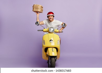 Food service, fast delivery concept. Impatient pizza delivery driver poses on fast motorbike, being in hurry with boxes of fast food, clenches teeth, annoyed with heavy traffic drives to customer home