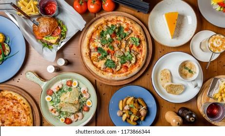 Food set of european cuisine, pizza, Burger, salad caesar, potatoes and cream soup top view
