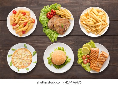 Food set pasta, bbq meat, french fries, pizza, burger and bbq salmon on the wooden background.