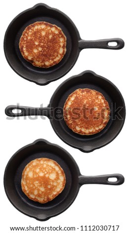 Food: set of three various pancakes on a black frying pan, isolated on white background