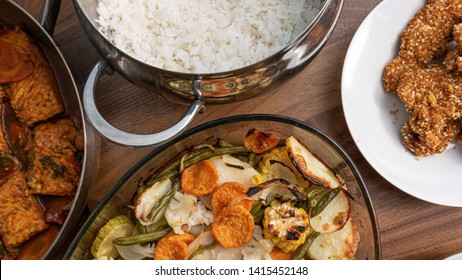 Food for Shabbat laid on a table. Rice, fish, gluten-free bread, chicken breast, chicken wings, baked vegetables.
