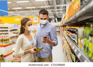 food shopping, consumerism and pandemic concept - happy couple wearing face protective medical masks for protection from virus disease with smartphone buying olive oil at grocery store or supermarket