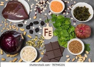 Food is source of ferrum. Various food rich in vitamins and micronutrients. Useful food for health and balanced diet. Prevention of avitaminosis. Small cutting board with name of ferrum. Top view