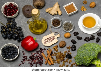 Food sources natural antioxidants. Antioxidants neutralize free radicals, have beneficial health effects. Group includes minerals, carotenoids and vitamins. Small board with word antioxidant. Top view