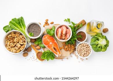 Lebensmittelquellen von Omega 3 und Omega 6 auf weißem Hintergrund, Draufsicht. Lebensmittel mit hohem Gehalt an Fettsäuren, einschließlich Gemüse, Meeresfrüchten, Nüssen und Samen