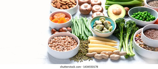 Food sources of plant based protein. Healthy diet with  legumes, dried fruit, seeds, nuts and vegetables.  Foods high in protein, antioxidants, vitamins and fiber. Image with copy space