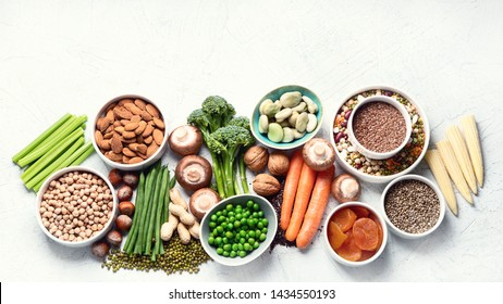 Food sources of plant based protein. Healthy diet with  legumes, dried fruit, seeds, nuts and vegetables.  Foods high in protein, antioxidants, vitamins and fiber.  Top view with copy space