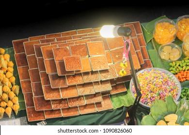 Food stall selling traditional thai desserts. Khanom moa gang ( thai custard cake), khanom tarn (palm heart muffin), Luke choop ( mung bean candy)