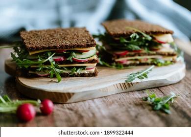 Food still life, fresh whole grain bread with cheese, radish, cucumber, arugula, healthy food, superfood