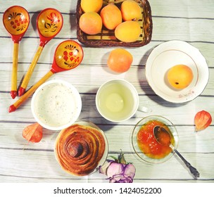 Food still life with Icelandic thick cultured milk called skyr, twist of bread, apricot jam, fresh apricots, green tea cup, wooden spoons as concept for healthy breakfast.