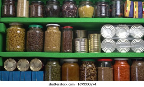 Food Stock Storage Shelf. Stocked home pantry ready for coronavirus quarantine and self-isolation. Long storage foods, drinks, supplies. Dry beans, rice, pasta, nuts, seeds, canned goods and vegetable