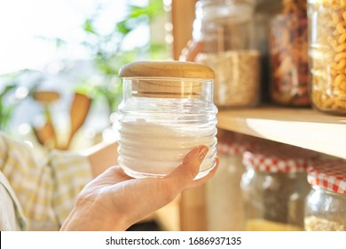 Food storage in pantry, woman holding jar of sugar in hand. Pantry interior, wooden shelf with food cans and kitchen utensils