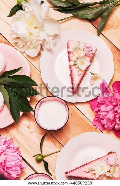 Food, food styling, cooking. Pink cakes and glass of milk with white and pink peonies