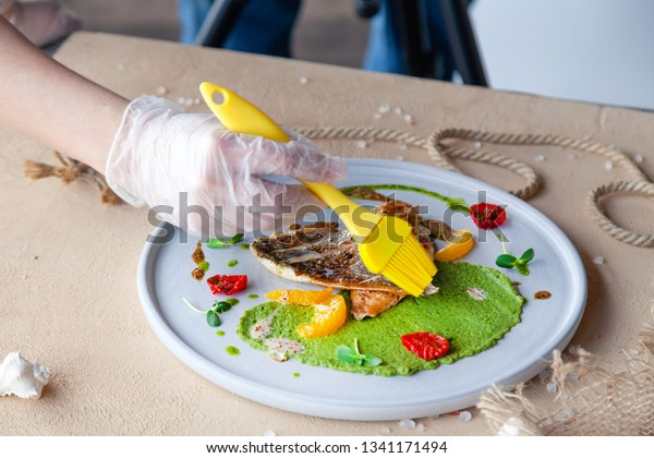 Food stylist with tassel preparing to shoot fried sea bass fillet with green pea puree, tomato, orange slices. Concept professional photography, photo session of new menu, flat-lay, freelance
