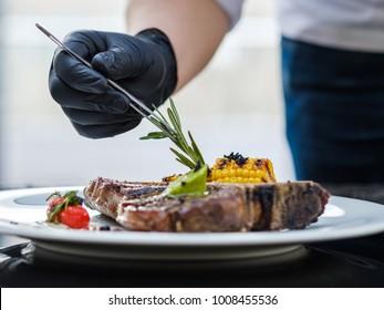 food stylist at work. Decorating meat steak meal. Culinary art. Creative arrangement