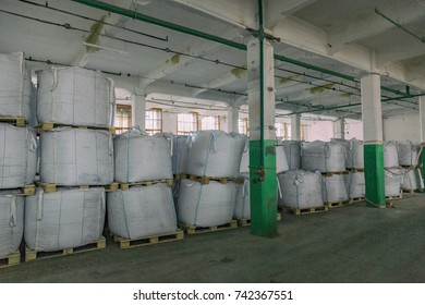 Food sugar in large white bags is stored in a food production warehouse