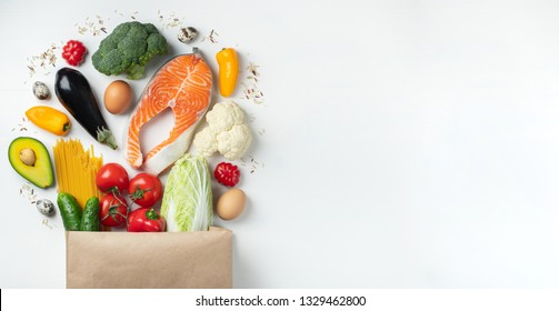 Food from the supermarket. Paper bag full of healthy food. Top view with copy space. Flat lay.