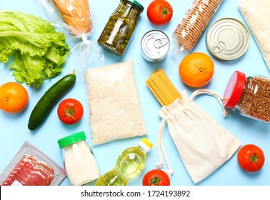Food supplies for the period of quarantine on blue background. Set of grocery items from canned food, vegetables, pasta, cereal. Food delivery concept. Donation concept. Top view.