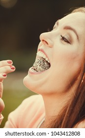 Food and sweets. Appetite and tasty meal dessert. Joyful woman with little cookie cupcake. Happy smiling girl eating small cake outdoor.