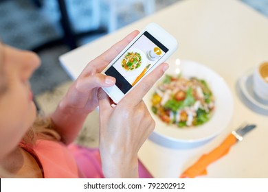 food, technology, eating and people concept - woman with smartphone photographing salad at restaurant