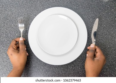 Food theme: African American hand show gesture on an empty white plate on a dark background in isolated top view, Healthy food, dark skin hands holding knife and fork on empty plate Anorexia concept