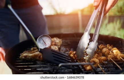 A food thermometer checking that chicken is being cooked correctly, safely on a barbecue on a sunny day in the garden as a man turns over kebabs with tongs.