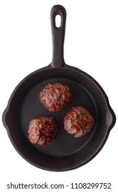 Food: three cooked homemade meatballs on a frying pan, isolated on white background