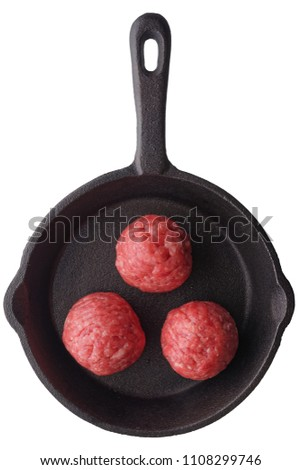 Food: three fresh uncooked homemade meatballs on a frying pan, isolated on white background