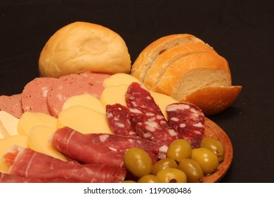 Food tray with delicious salami, pieces of sliced ham and chesses
