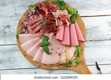 Food tray with delicious salami, pieces of sliced ham, sausage and salad. Meat platter with selection